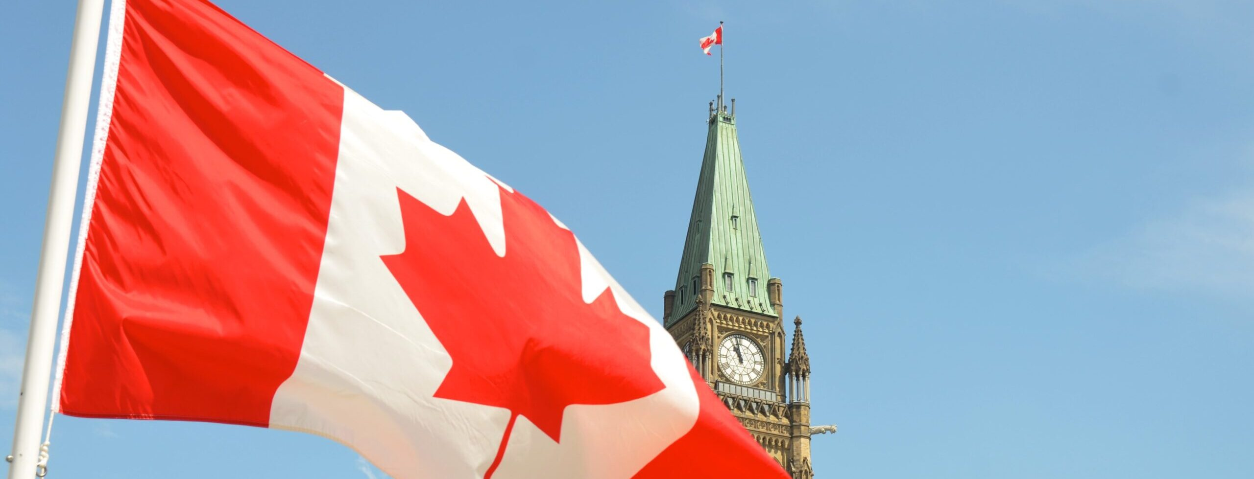 Canadian flag in front of the tower of the central block of parliament in Ottawa