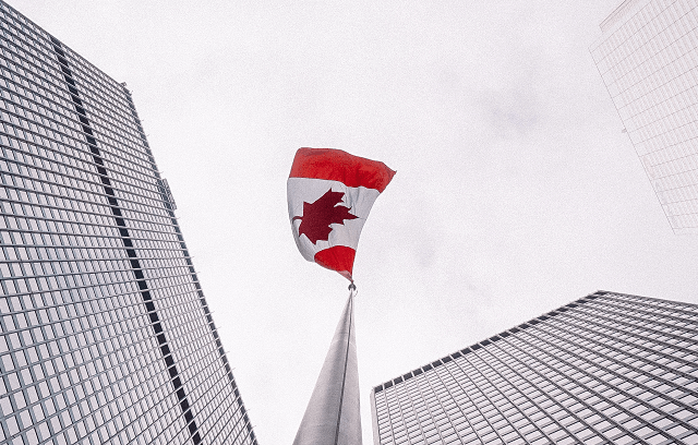 A Step by Step Guide to Federal Incorporation in Canada - Canadian flag between buildings against a white sky